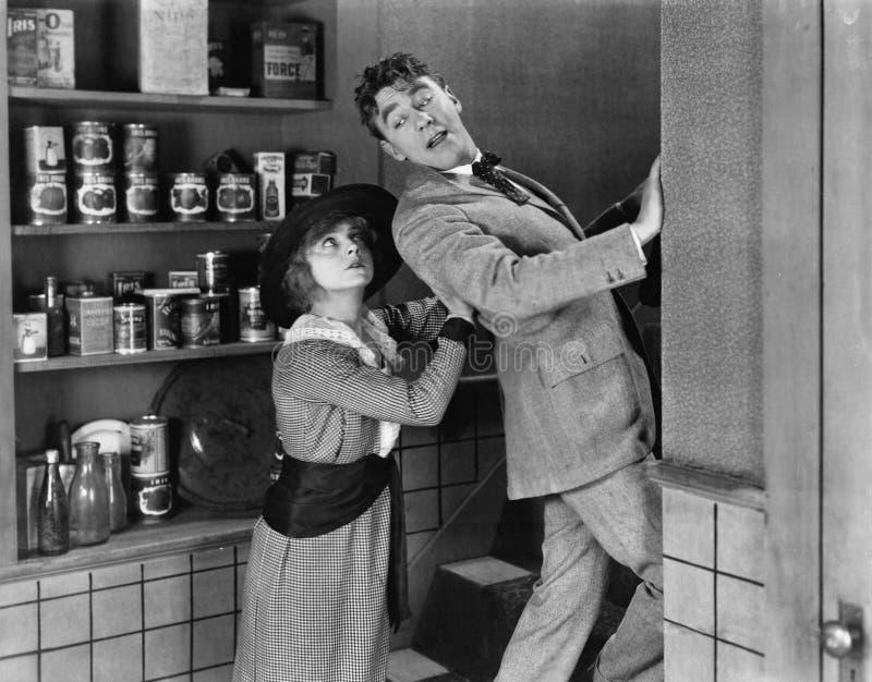 Perfil de uma jovem mulher que elimina um homem novo de uma cozinha doméstica (todas as pessoas descritas não são umas vivas mais fotos de stock