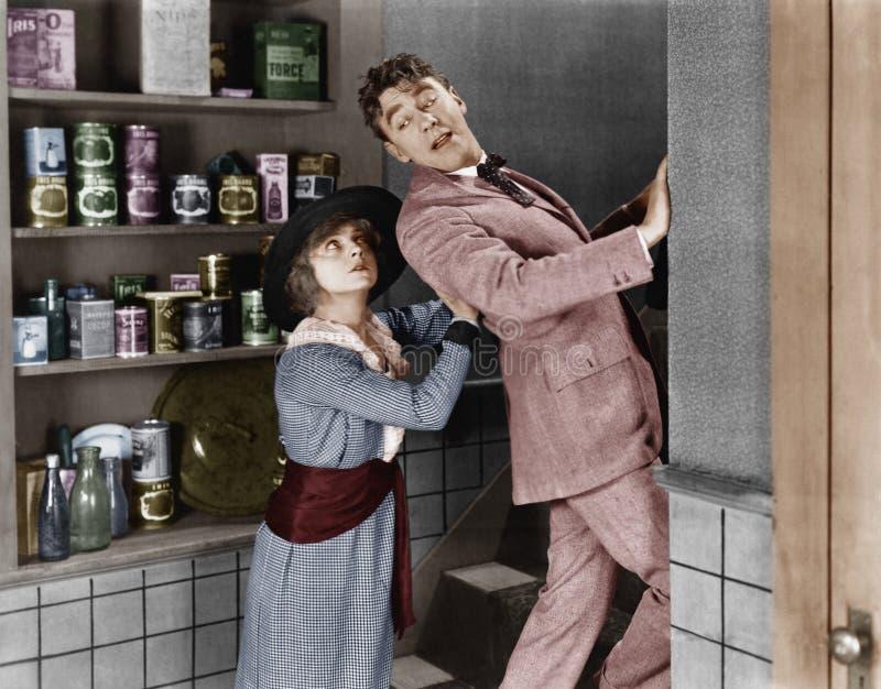 Perfil de uma jovem mulher que elimina um homem novo de uma cozinha doméstica (todas as pessoas descritas não são umas vivas mais imagem de stock