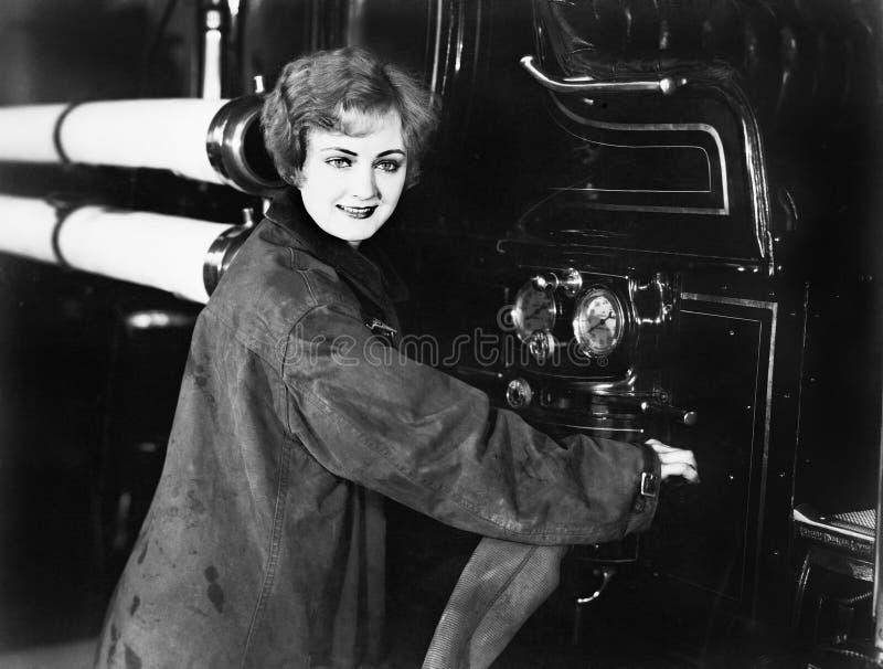 Perfil de uma jovem mulher que está perto de um carro de bombeiros que une uma mangueira (todas as pessoas descritas não são umas foto de stock