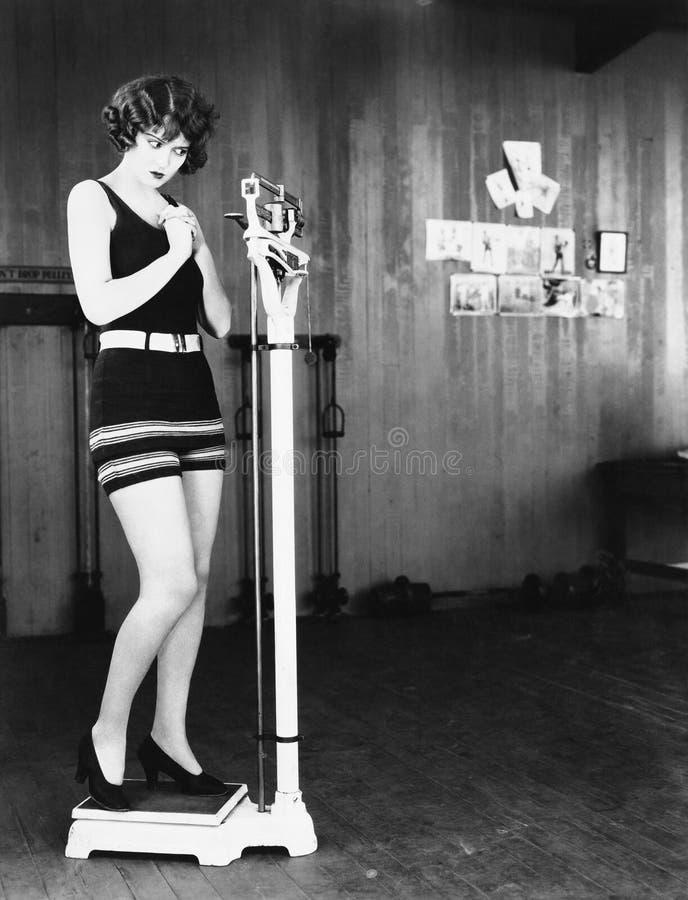 Perfil de uma jovem mulher que mede seu peso em uma escala de peso (todas as pessoas descritas não são umas vivas mais longo e ne foto de stock