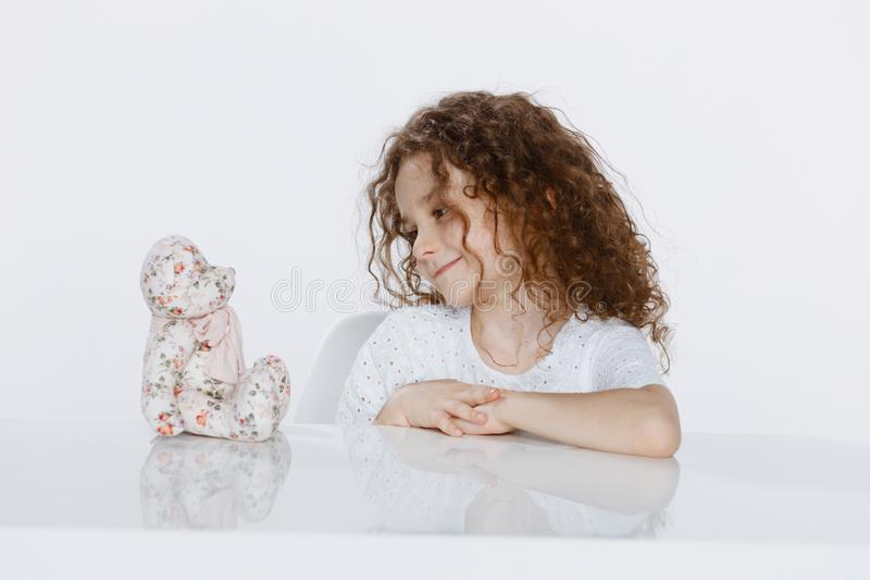 Perfil de uma menina encaracolado pequena alegre assentada em uma tabela que olha no brinquedos, sobre o fundo branco imagens de stock