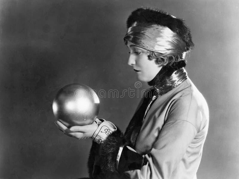 Perfil de uma mulher que guarda uma bola de metal (todas as pessoas descritas não são umas vivas mais longo e nenhuma propriedade imagens de stock