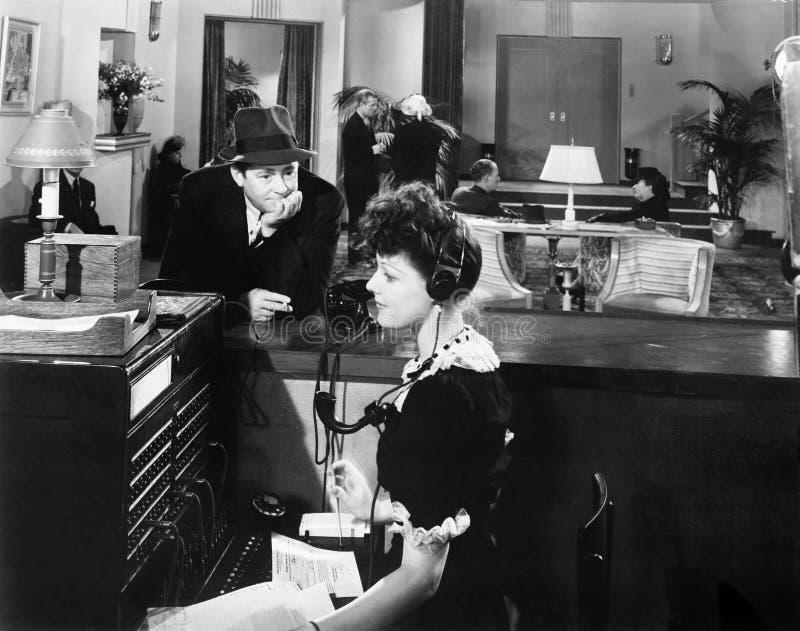 Perfil de uma mulher que trabalha no painel de comando do telefone com um homem que olha a (todas as pessoas descritas não são um foto de stock
