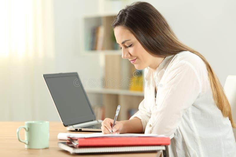 Perfil de un estudiante que toma notas en casa foto de archivo