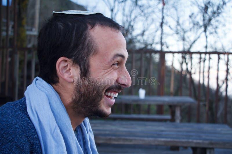 Perfil de un hombre judío joven en un tocado judío tradicional de Kippa que habla, sonrisa, fumando encima del monte Vesubio en N fotos de archivo