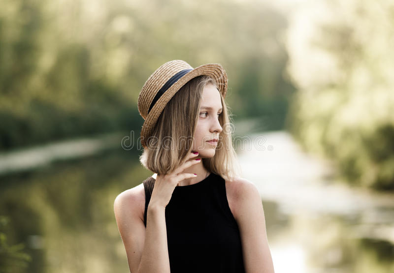 Perfil de una muchacha bonita con el pelo corto en un sombrero de paja sobre nacional imagenes de archivo