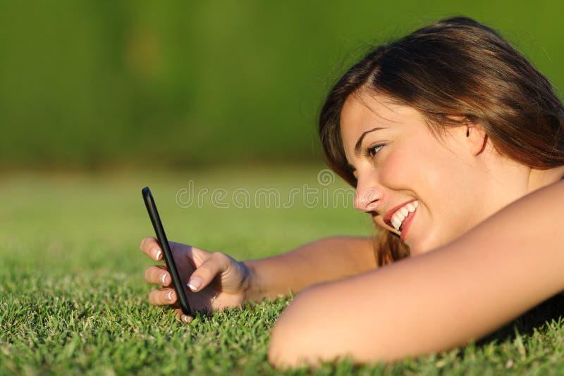 Perfil de una muchacha divertida que usa un teléfono elegante en la hierba fotografía de archivo