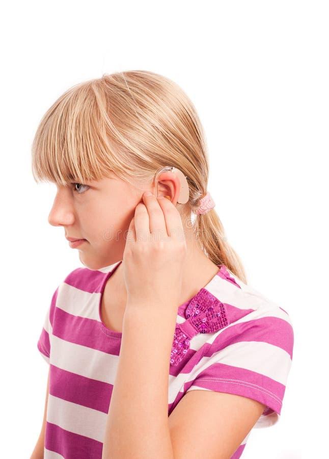 Perfil de una muchacha perjudicada con el audífono imágenes de archivo libres de regalías