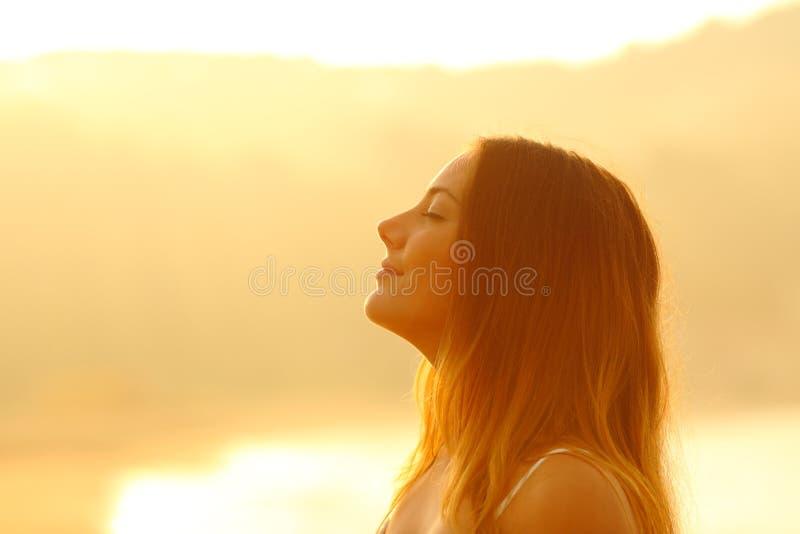 Perfil de una mujer en la puesta del sol que respira el aire fresco fotos de archivo