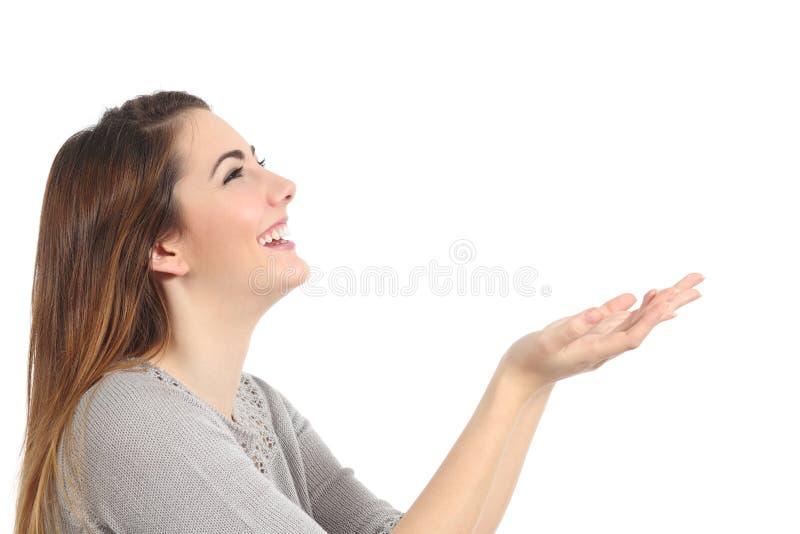 Perfil de una mujer feliz que lleva a cabo algo en blanco imagenes de archivo