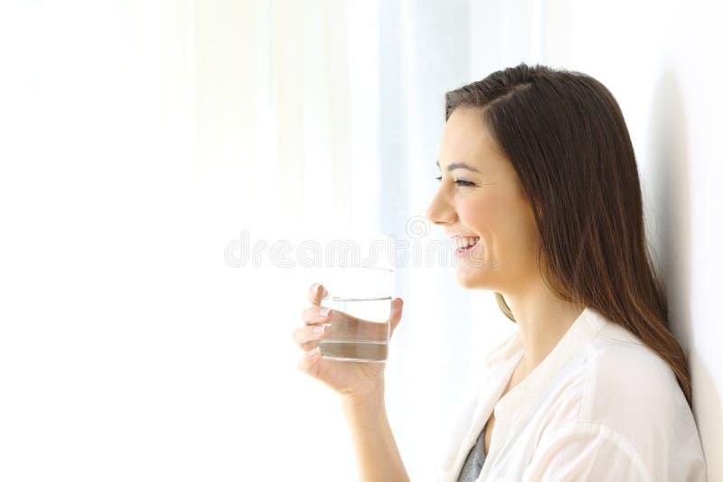 Perfil de una mujer feliz que sostiene un vidrio de agua fotos de archivo libres de regalías