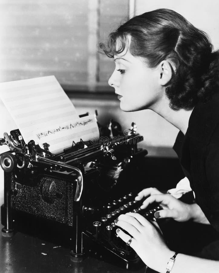 Perfil de una mujer joven que mecanografía notas musicales con una máquina de escribir (todas las personas representadas no son v imagen de archivo