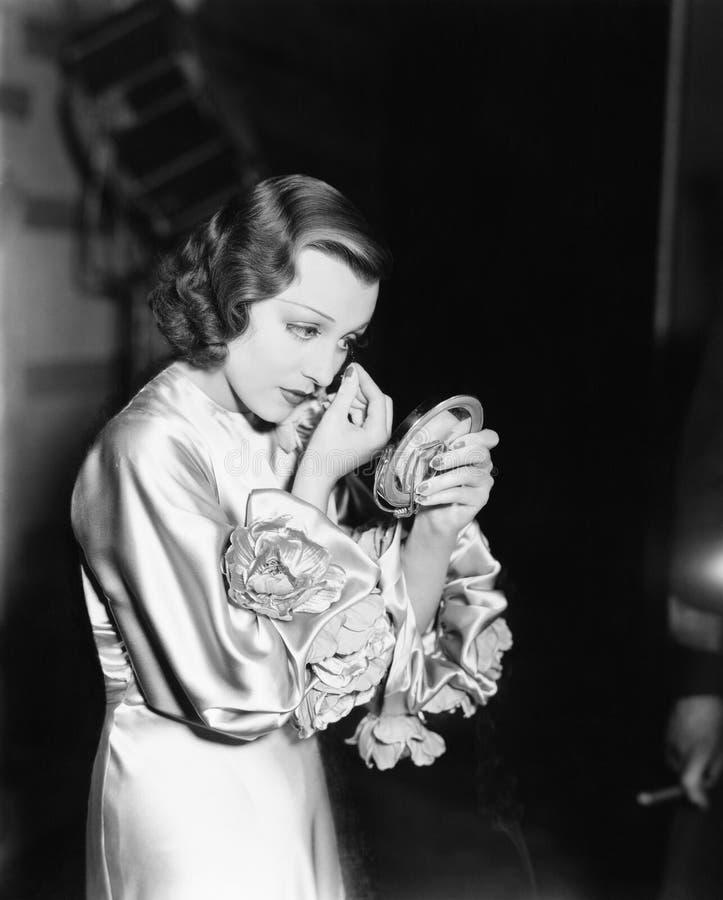 Perfil de una mujer joven que mira en un espejo y que limpia su ojo (todas las personas representadas no son un ningún del estado fotos de archivo