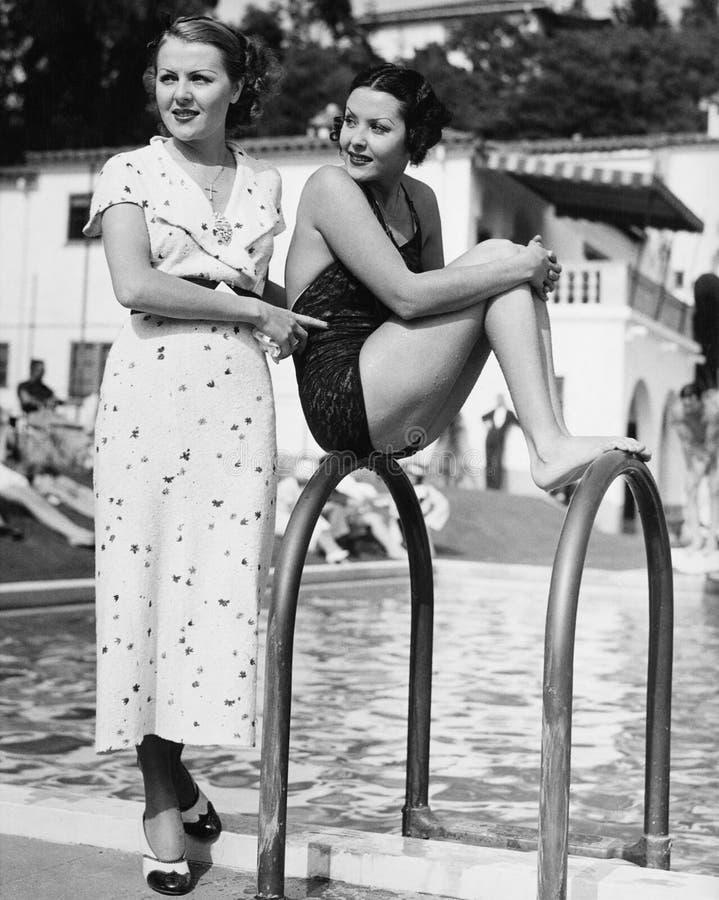 Perfil de una mujer joven que se sienta en una escalera en el lado de la piscina con otra mujer que se coloca detrás de ella (tod imagenes de archivo