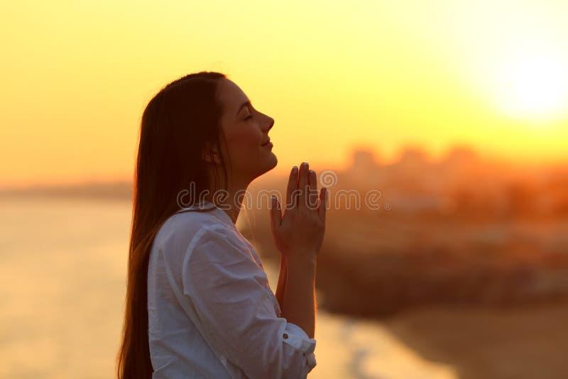 Perfil de una mujer que ruega en la puesta del sol imagenes de archivo