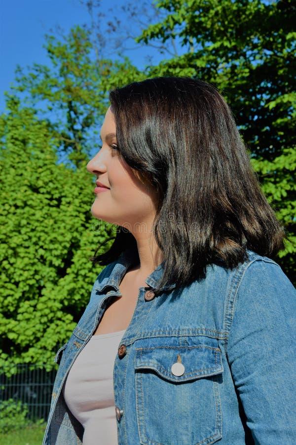 Perfil de una mujer satisfecha joven en el parque imagen de archivo libre de regalías