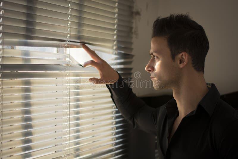 Perfil del hombre joven que mira a escondidas a través de las persianas foto de archivo libre de regalías