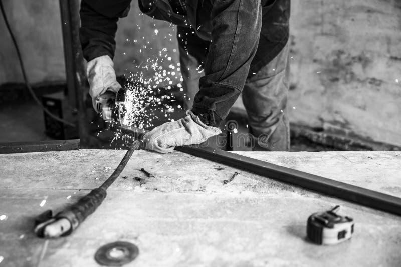 Perfil del metal del corte del trabajador con la amoladora de ángulo eléctrica Gente en el trabajo, profesión Efecto monocromátic fotografía de archivo