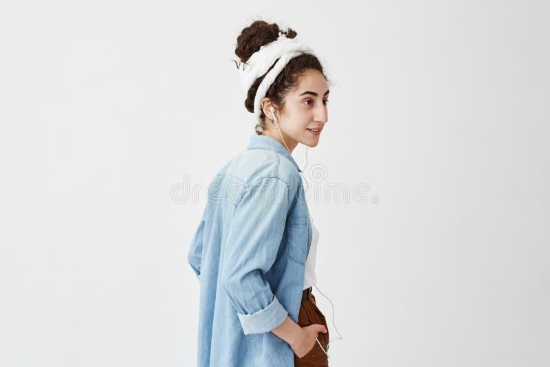 Perfil do adolescente fêmea que escuta a música ou o livro audio ao ir à universidade, tendo a expressão feliz, rindo imagem de stock royalty free