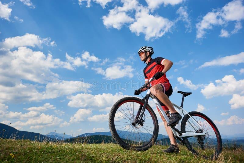 Perfil do motociclista atlético novo do turista no sportswear profissional que começa dar um ciclo uma bicicleta imagens de stock royalty free