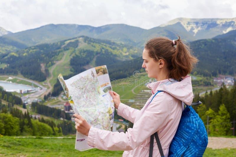Perfil do turista novo atrativo que está sendo perdido em sua maneira, olhando o mapa atentamente, procurando pela rota apropriad foto de stock royalty free