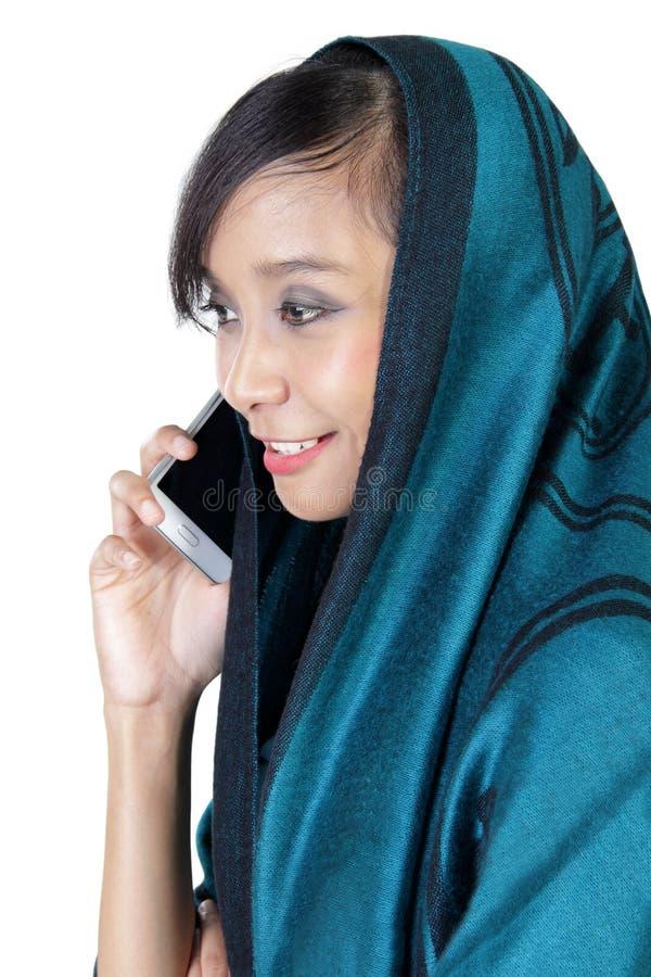 Perfil lateral da mulher muçulmana que faz o telefonema fotografia de stock