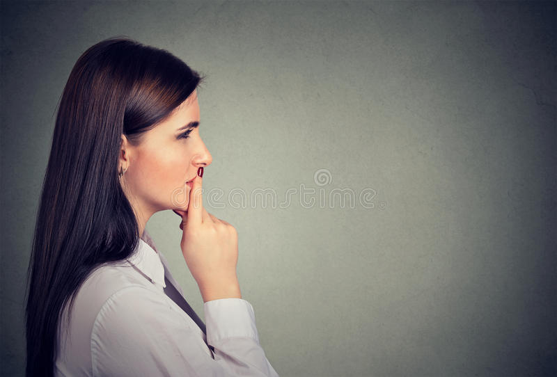 Perfil lateral de una mujer joven pensativa imagen de archivo