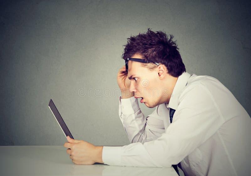 Perfil lateral homem chocado que olha o laptop foto de stock royalty free