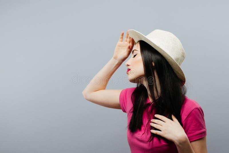 Perfil modelo femenino hermoso que presenta con un sombrero imagen de archivo