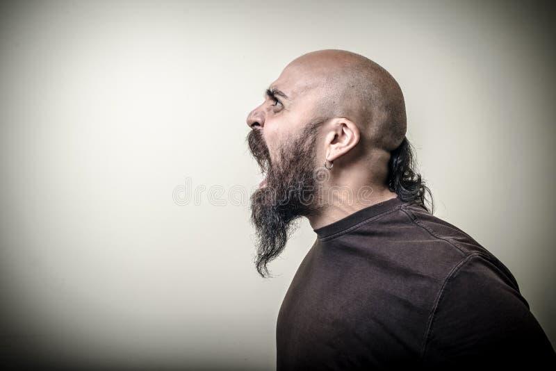 Perfil que grita al hombre barbudo enojado foto de archivo