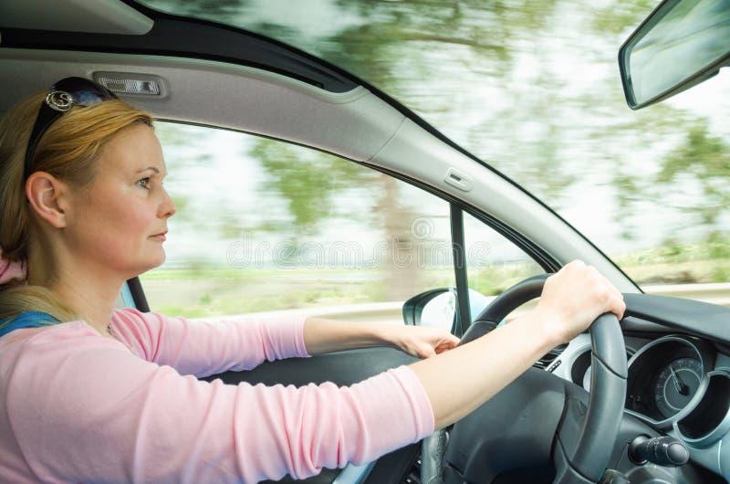 Perfile el retrato de la conducción carefullly segura tranquila seria de la mujer fotografía de archivo libre de regalías