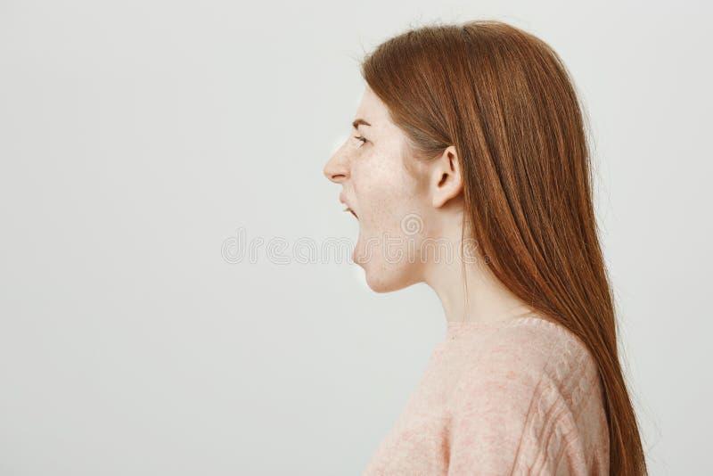 Perfile el retrato de la mujer caucásica del pelirrojo lindo con las pecas que grita hacia fuera ruidosamente y que está enojada  fotos de archivo libres de regalías