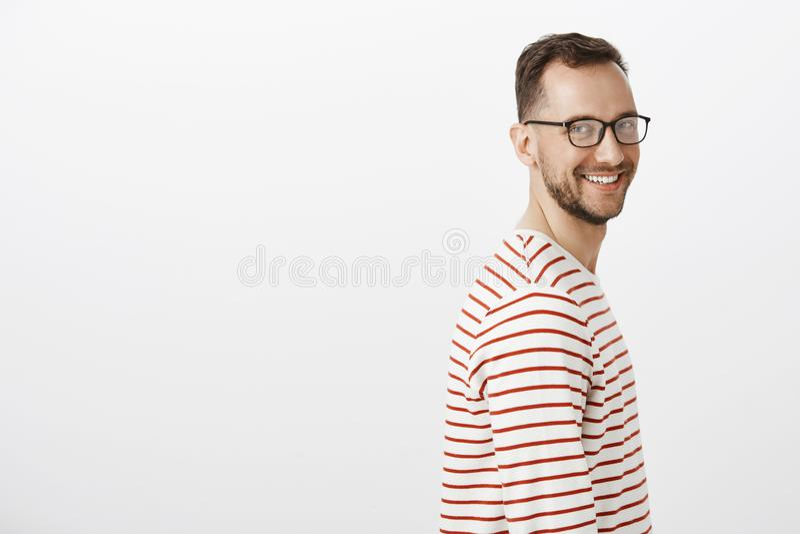 Perfile el retrato del individuo caucásico de amistoso-mirada despreocupado con la barba en vidrios negros, dando vuelta y sonrie fotografía de archivo