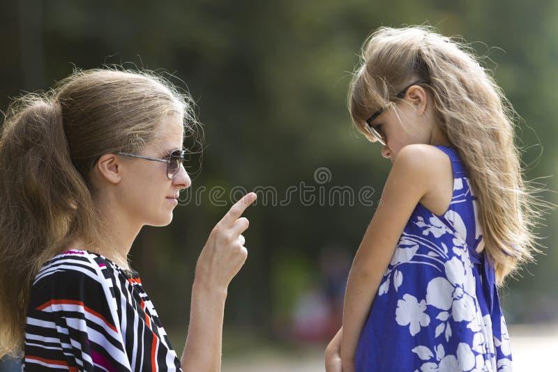 Perfile el retrato del primer de la mujer rubia joven frustrada que habla con la pequeña muchacha joven del niño fotografía de archivo libre de regalías