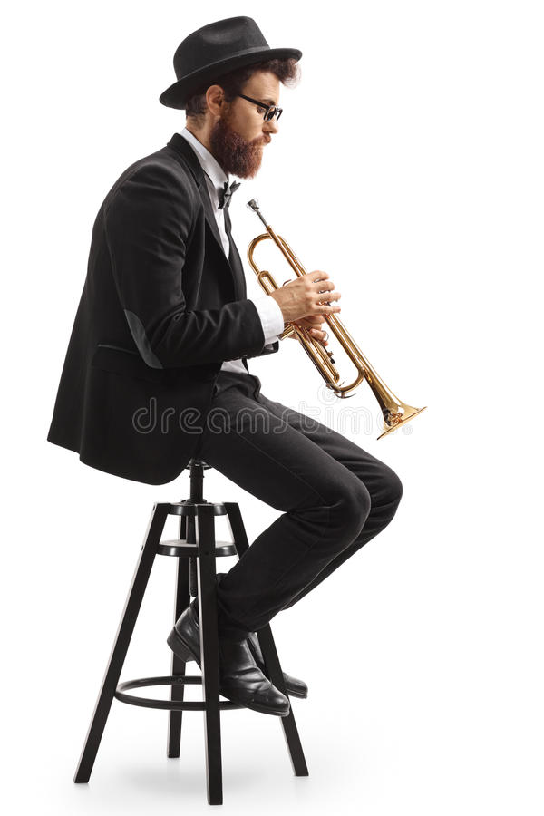Perfile el tiro de un jugador de trompeta asentado en una silla imagenes de archivo