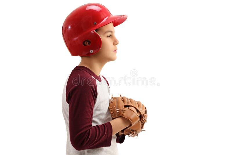 Perfile el tiro de un muchacho con un guante de béisbol y un casco fotografía de archivo libre de regalías