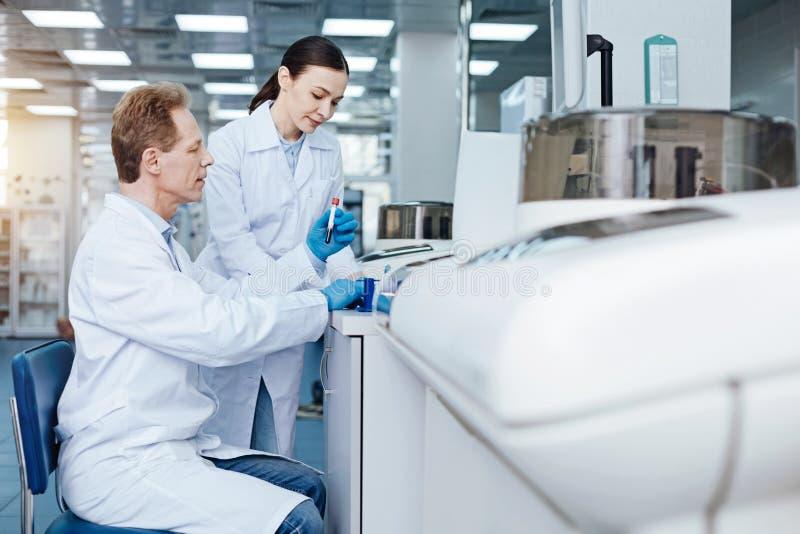 Perfile a foto do médico masculino que senta-se em seu local de trabalho imagens de stock