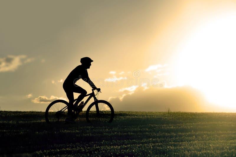 Perfile la bici de montaña del campo a través del montar a caballo del hombre del deporte de la silueta fotografía de archivo