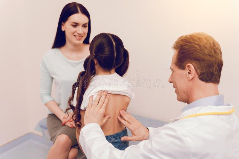 Perfile la foto del doctor competente ese niño de examen fotografía de archivo libre de regalías
