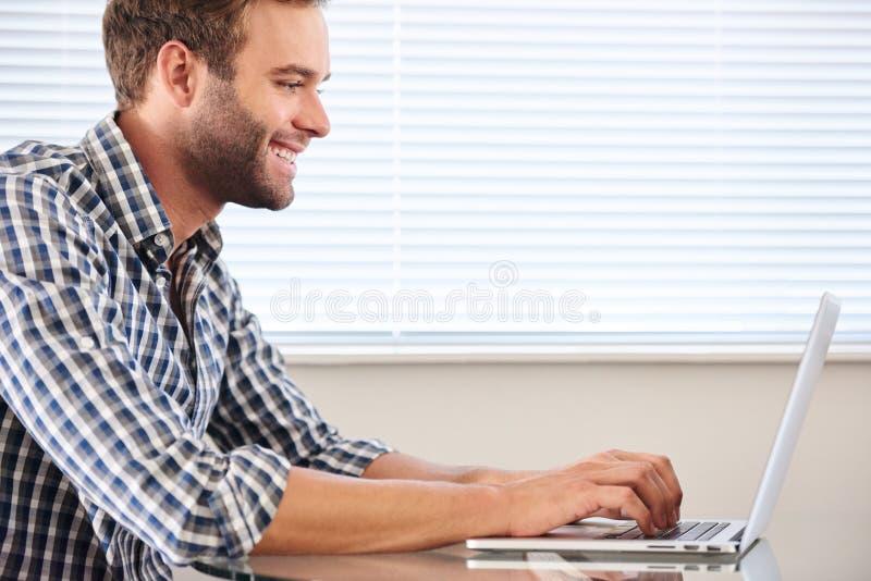 Perfile la imagen del hombre preparado hermoso que mecanografía en el ordenador portátil imagen de archivo
