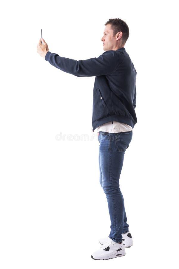 Perfile la opinión el hombre adulto casual moderno que toma las fotos con el teléfono móvil imágenes de archivo libres de regalías