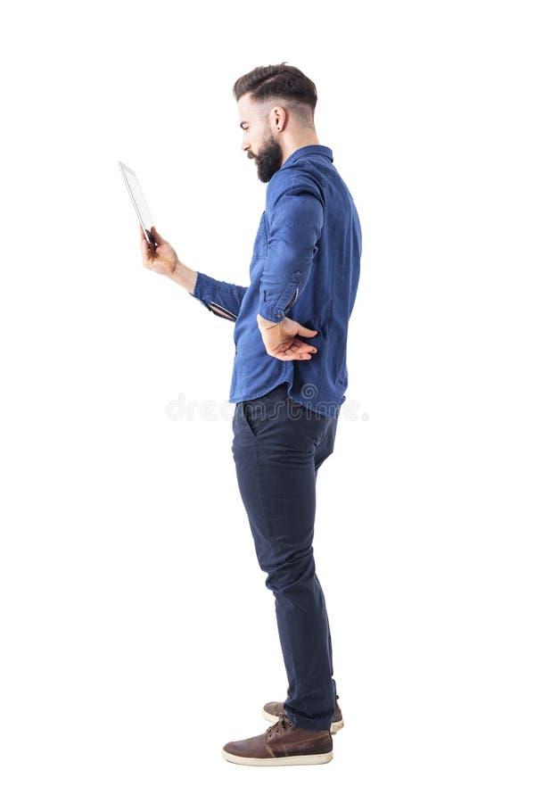 Perfile la opinión el hombre de negocios barbudo serio que sostiene y que mira la tableta fotografía de archivo