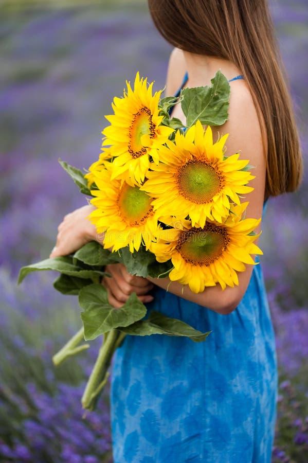 Perfile la opinión la mujer joven que sostiene un ramo de la flor fotografía de archivo libre de regalías