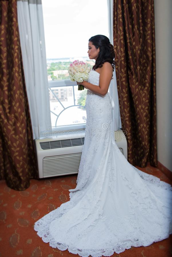 Perfile la opinión una novia que sostiene su ramo por una ventana, vista lateral del retrato nupcial foto de archivo