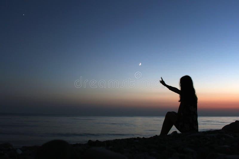 Perfile la silueta de una mujer que considera en la playa la puesta del sol fotografía de archivo