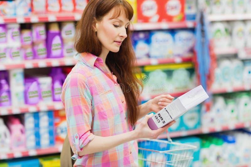 Perfile a opinião a mulher com o cesto de compras que guarda o produto fotografia de stock
