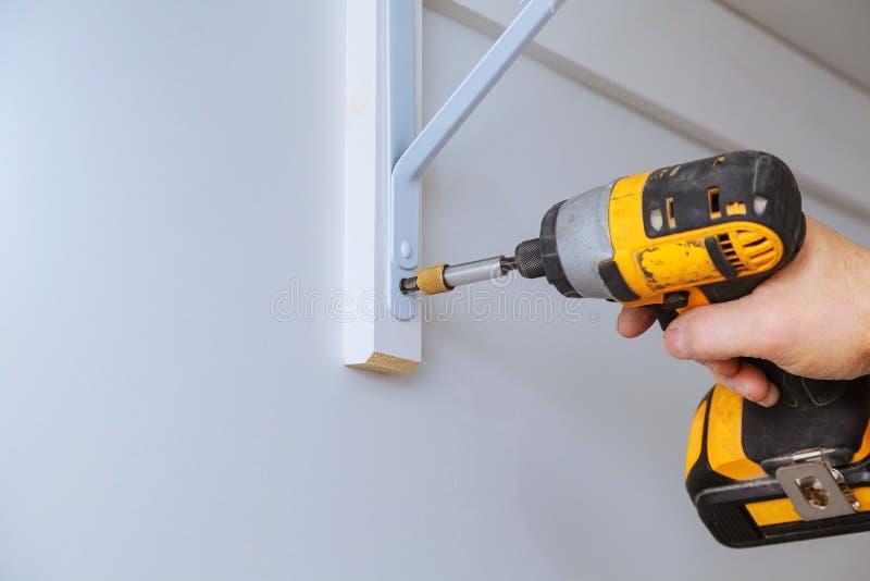 Perfile a opinião um trabalhador manual bonito que faz alguma broca para murar a instalação de uma prateleira fotografia de stock royalty free