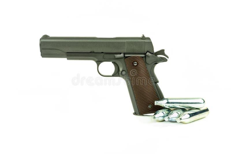 Perfile a vista do revólver semiautomático isolado do airsoft com recipiente do gás Réplica do revólver real no fundo branco imagem de stock
