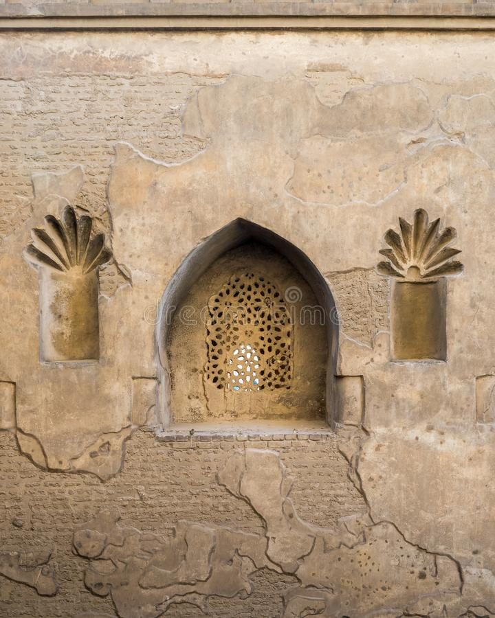 Perforated arched stucco window decorated with floral patterns, Outer wall of Mosque of Ibn Tulun, Medieval Cairo, Egypt royalty free stock photo