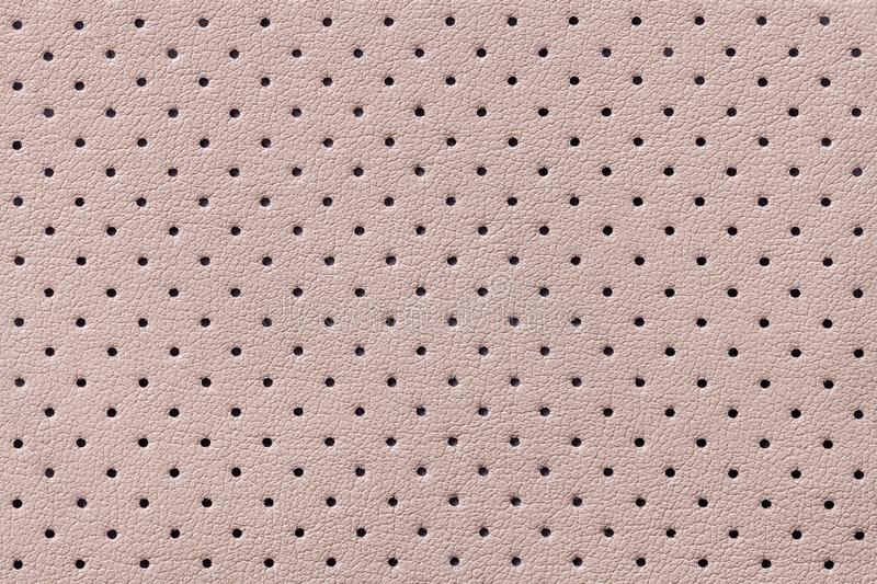 Perforated beige leather texture background, closeup. Light brown backdrop from wrinkle skin stock image